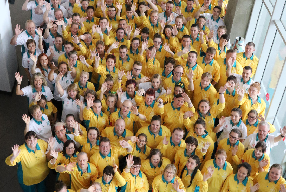A group of people in green and gold waving at the camera